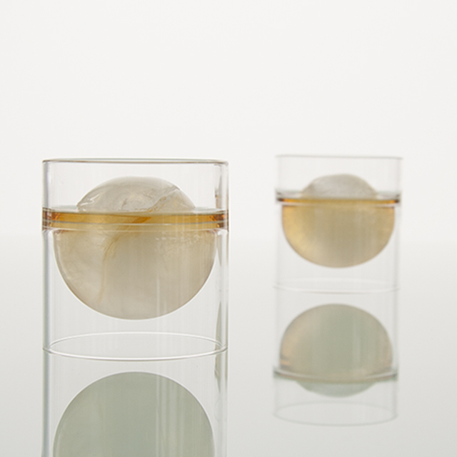 A pair of float tea cups with whiskey over Japanese ice balls.