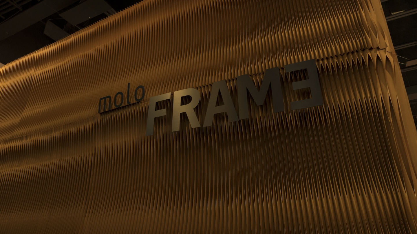 Signs for molo and FRAME hanging from softwall.