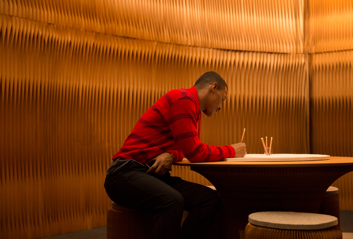 A man writes on cantilever table, a round table made from paper and MDF.