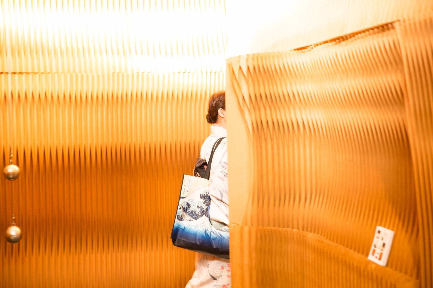 A woman in a kimono passes through a door made from paper walls. accordion portable partition walls by molo