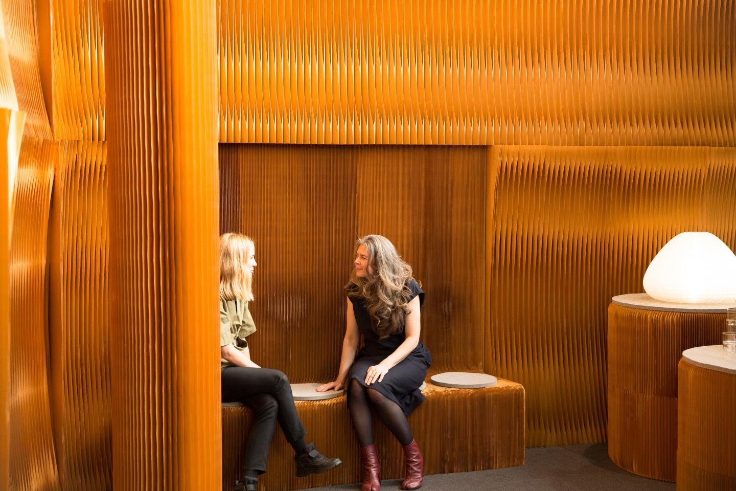 Two women sit and chat on a paper benchwall at M&O 2018. Paper furniture by molo