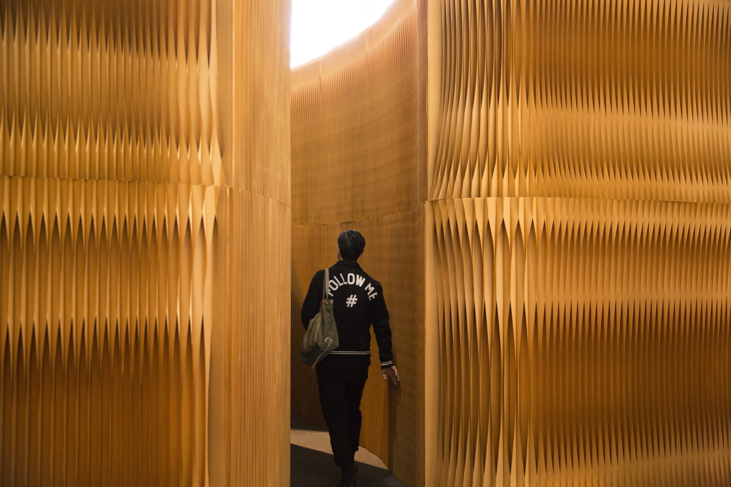 A man strolls through a corridor made from paper softwall. accordion portable partition walls by molo