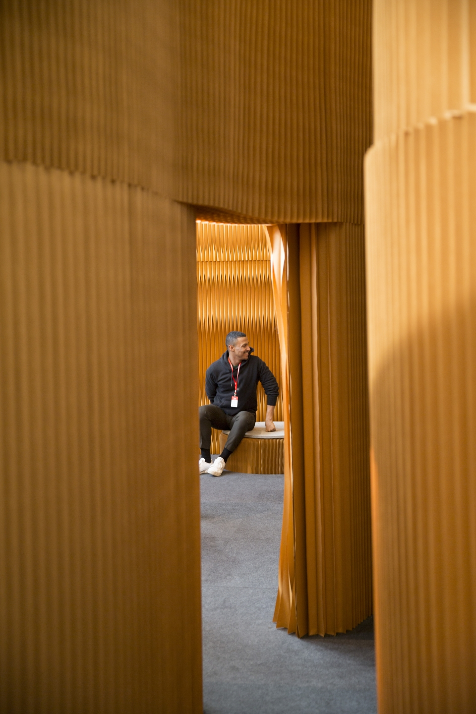 A man relaxes on softseating, molo's flexible paper seat. display of accordion portable partition walls by molo