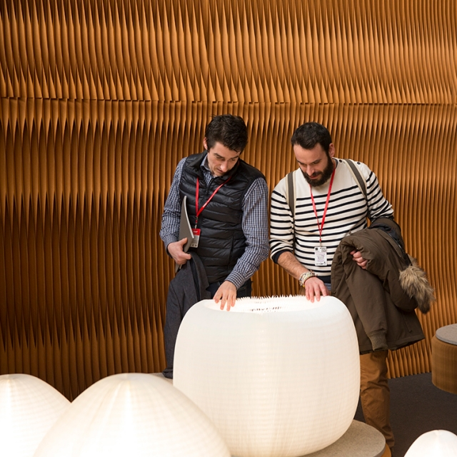 Two men peek inside urchin softlight at Maison et Objet.