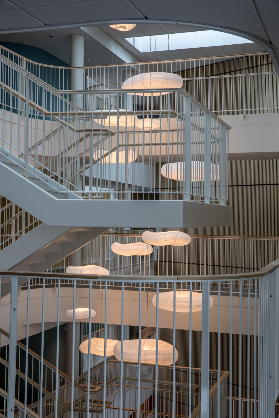 cloud softlight pendant fills the space around an open staircase.