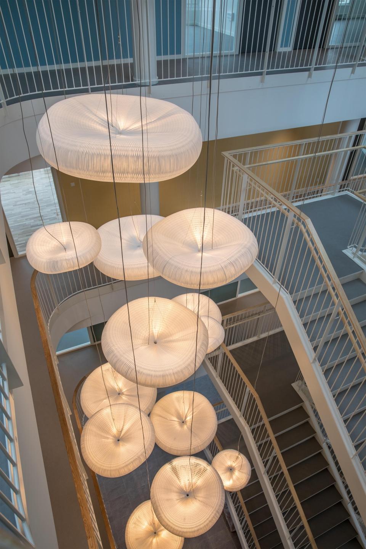 Looking down a cascading arrangement of cloud softlight pendants.