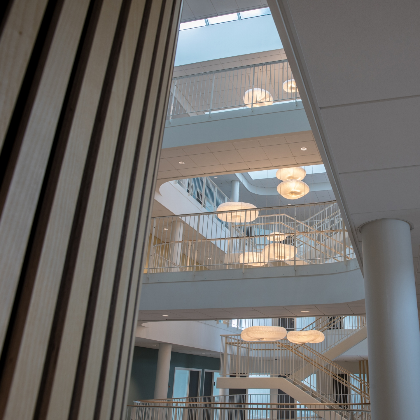A distance view of cloud softlight pendants hanging in an atrium.