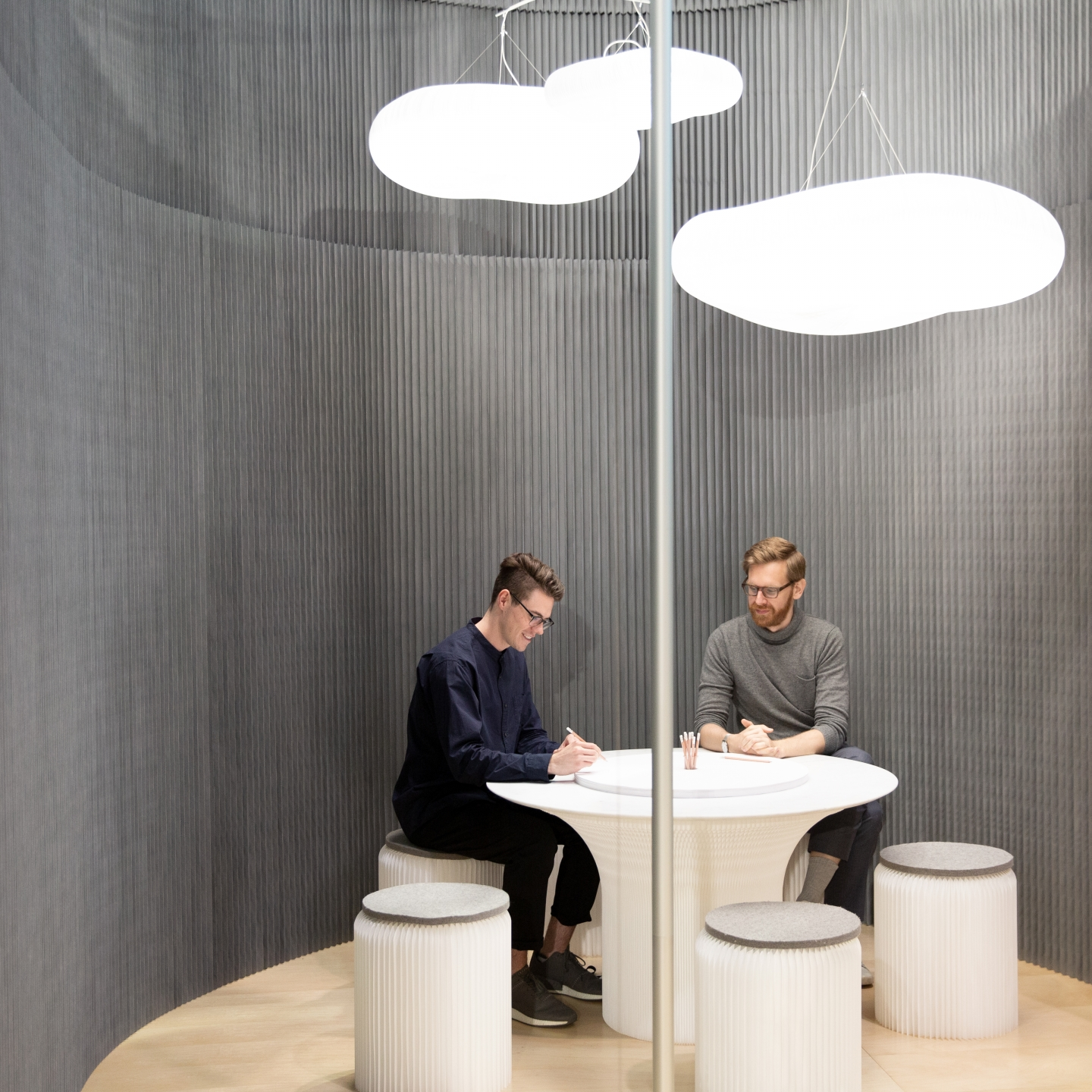 A cantilever table underneath cloud mast at ICFF 2018. custom gray wall partitions