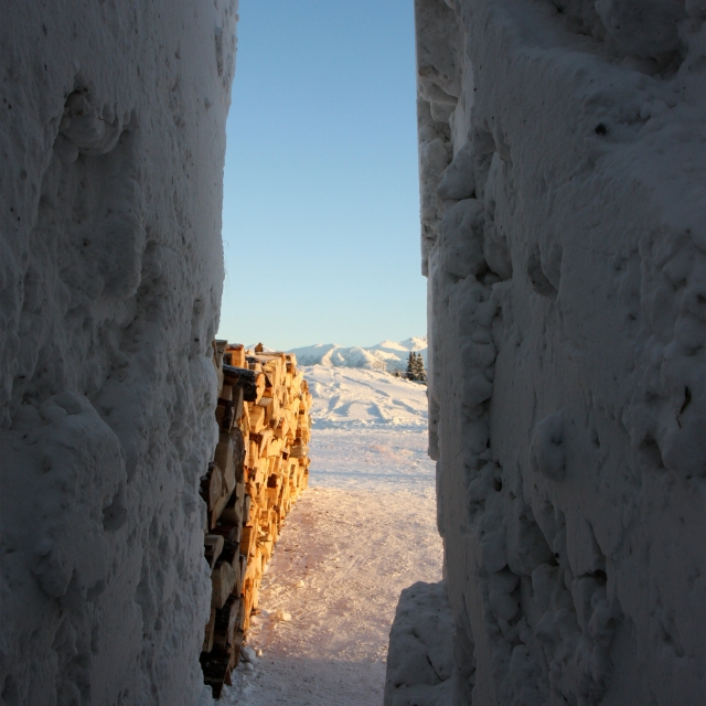 stacked firewood rests beside an opening between towering walls of snow. northern sky circle was an installation in Alaska designed by Stephanie Forsythe + Todd MacAllen, in collaboration with sound artist Ethan Rose.