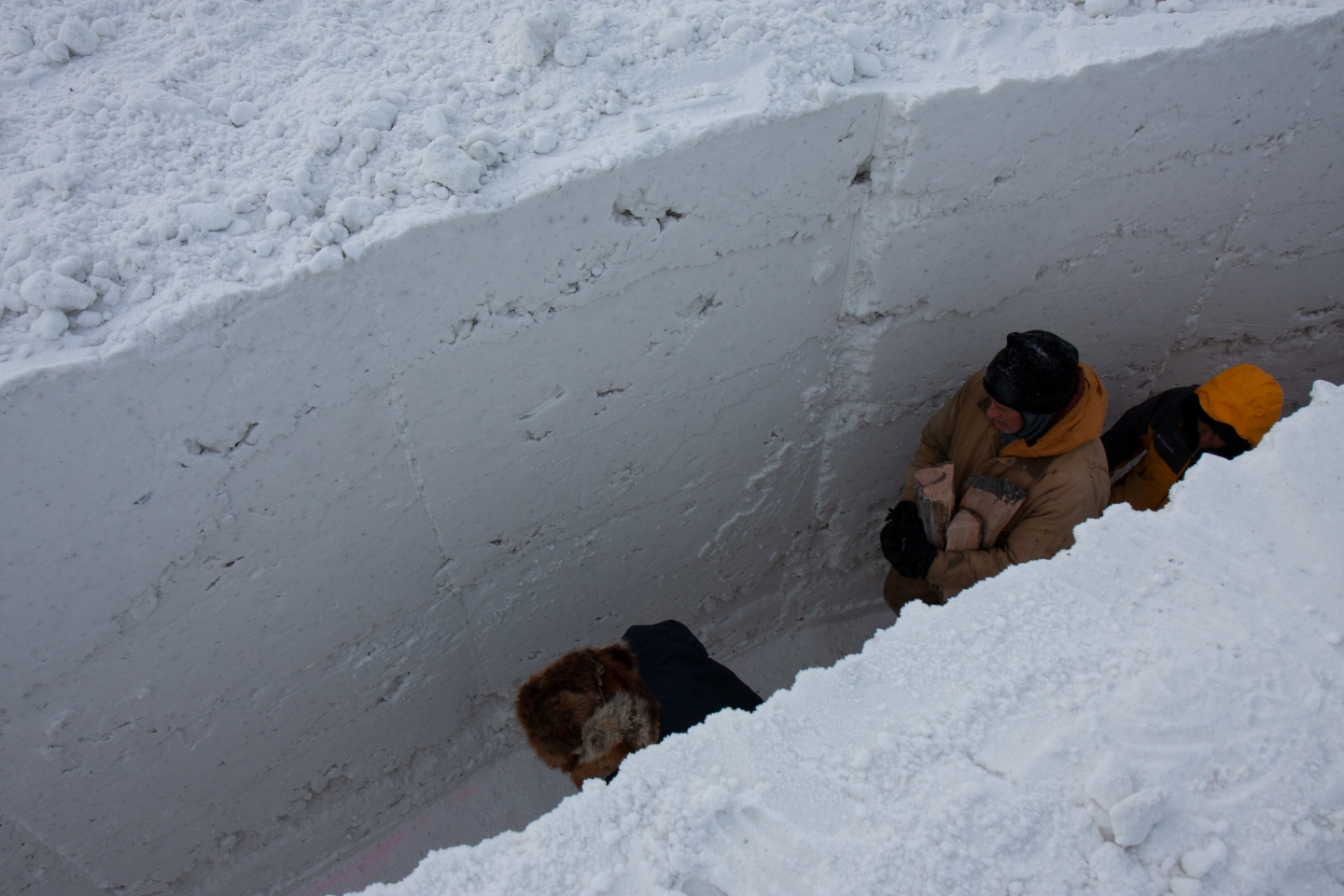 Two men carry firewood through a snow maze in Alaska. northern sky circle is a maze of snow and ice designed by Stephanie Forsythe + Todd MacAllen, in collaboration with sound artist Ethan Rose.