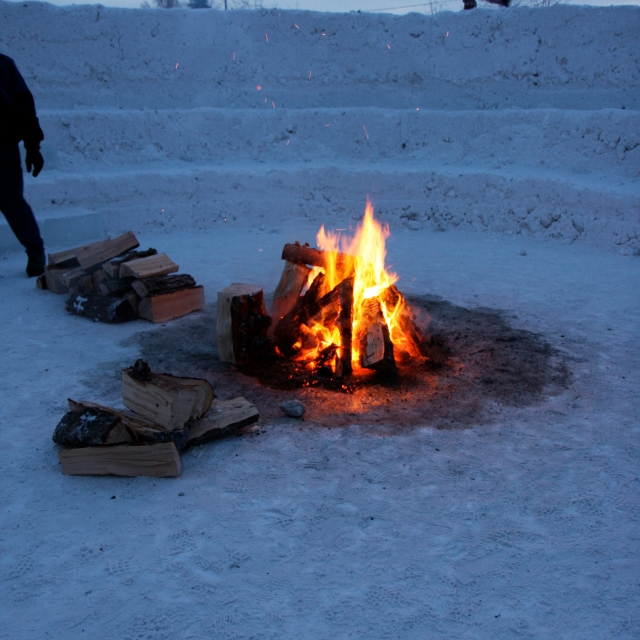 a camp fire provides a hearth at the heart of northern sky circle, an outdoor room of snow designed by Stephanie Forsythe + Todd MacAllen, in collaboration with sound artist Ethan Rose.