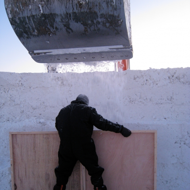a man builds a wall with snow and ice in Alaska. northern sky circle explores an architecture of elements.