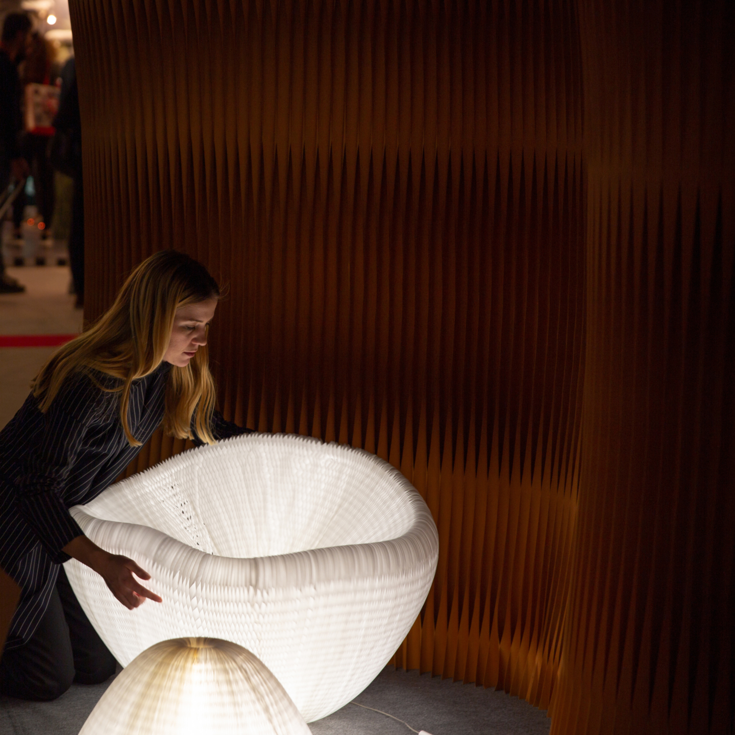 woman interacts with shape shifting urchin softlight paper lamp.